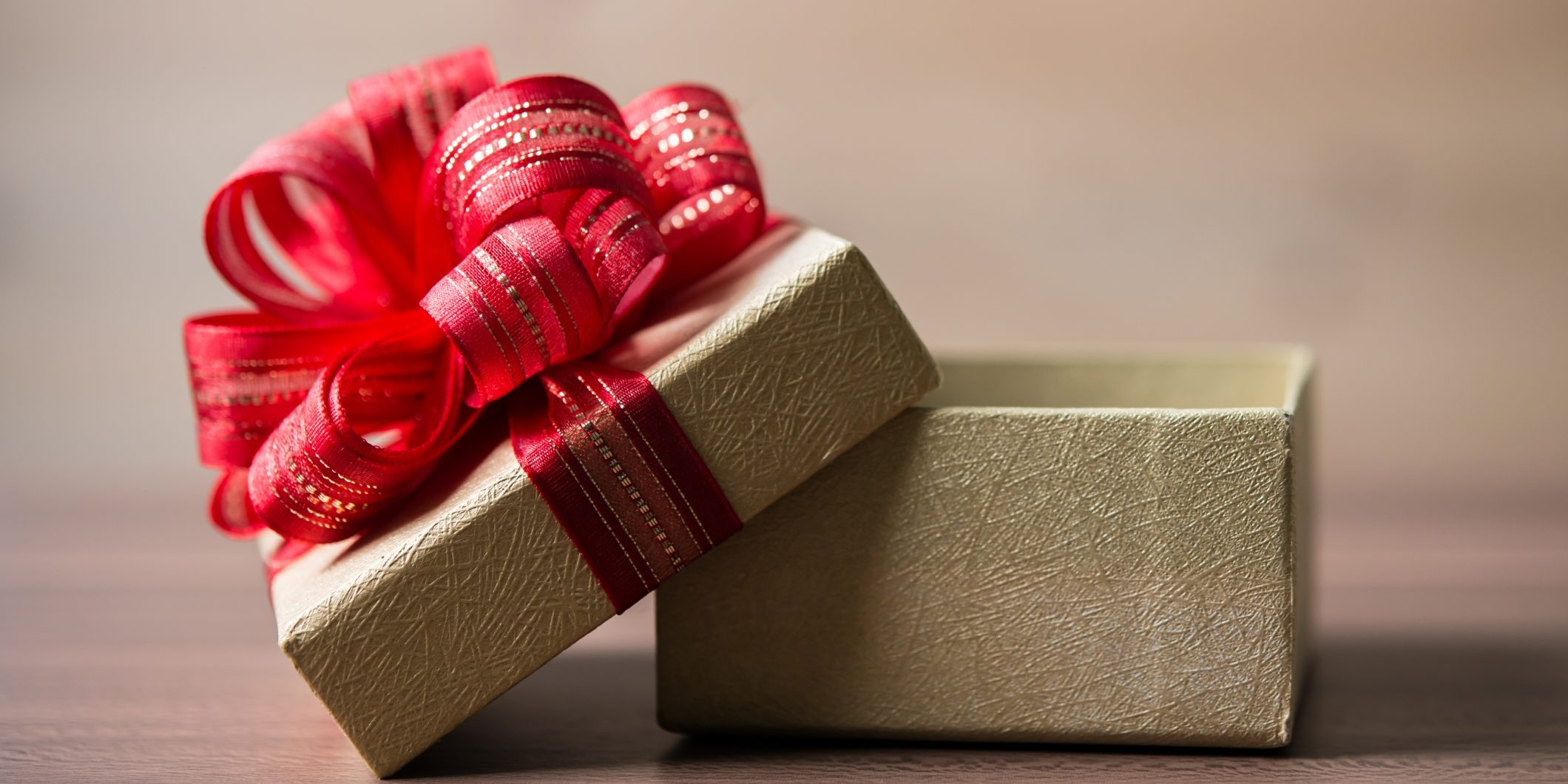 holiday packaging image with brown paper and red ribbon